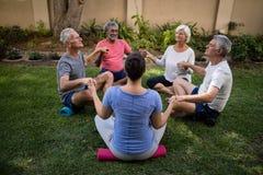 Instruktör- och pensionärfolk som mediterar, medan rymma händer royaltyfria foton