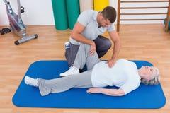 Instruktör som arbetar med den höga kvinnan på den matta övningen Royaltyfri Foto