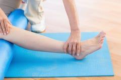 Instruktör som arbetar med kvinnan på den matta övningen Royaltyfria Foton