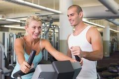 Instruktör som hjälper kvinnan med motionscykelen på idrottshallen Arkivfoton
