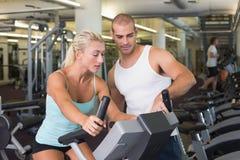 Instruktör som hjälper kvinnan med motionscykelen på idrottshallen Royaltyfri Foto