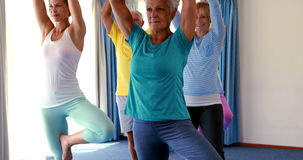 Instruktör som hjälper pensionärer i praktiserande yoga stock video