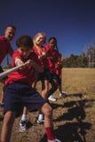 Instruktör som hjälper ungar i dragkamp under utbildning för hinderkurs arkivbilder