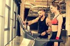 Instruktör som instruerar den sportiga kvinnan på trampkvarnen i idrottshall royaltyfri fotografi
