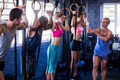 Instruktör som instruerar folk som rymmer gymnastiska cirklar Royaltyfria Foton