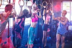 Instruktör som instruerar folk som rymmer gymnastiska cirklar Royaltyfri Bild