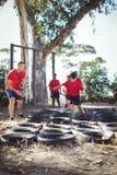 Instruktör som instruerar ungar under utbildning för däckhinderkurs fotografering för bildbyråer