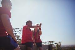 Instruktör som ser flickor som till varandra ger höjdpunkt fem under utbildning för hinderkurs Arkivbild