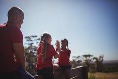 Instruktör som ser flickor som till varandra ger höjdpunkt fem under utbildning för hinderkurs Fotografering för Bildbyråer