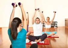 Instruktör som tar övningsgrupp på idrottshallen Royaltyfri Foto