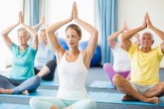 Instruktör som utför yoga med pensionärer royaltyfria bilder