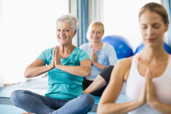 Instruktör som utför yoga med pensionärer royaltyfri foto