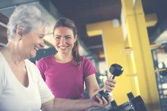 Instruktörarbeteövning med den höga kvinnan i idrottshallen royaltyfri foto