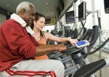 InstruktörAssisting Man On motionscykel på klubban arkivbilder