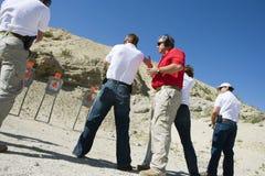 InstruktörAssisting People Aiming vapen på skjutavstånd royaltyfria foton