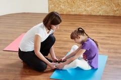 Instruktören hjälper en flicka att göra sträckning arkivfoto