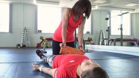 Instruktören kopplar av muskler av avvärja efter utbildningen stock video