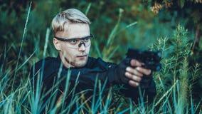 Instruktören med vapnet i skog leder att sikta och att posera på kamera fotografering för bildbyråer