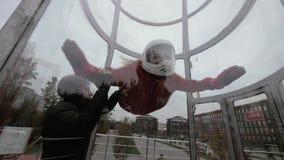 Instruktören undervisar kvinnan som hoppar med fritt fall i vindtunnel Kvinnaflyg i vindtunnel lager videofilmer