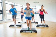 Instruktor z sprawności fizycznej klasy spełniania kroka aerobikami ćwiczy z dumbbells Zdjęcia Royalty Free