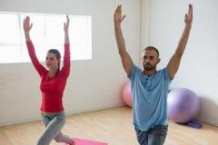 Instruktor z studencką ćwiczy wojownika 1 pozą w joga studiu Zdjęcia Royalty Free