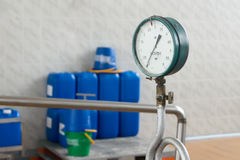 Instrument de mesure vissé dans le tuyau sur un fond de bleu Photographie stock