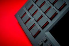 Instrument de musique, échantillonneur sur un fond rouge Image stock