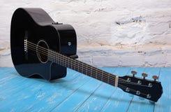 Instrument de musique - backgro coupé noir de brique de guitare acoustique Photographie stock