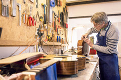 Instrument maker repairing an old acoustic guitar. Luthier - instrument maker - applying masking tape to an old acoustic guitar body with another guitar in the Royalty Free Stock Photography
