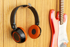 Instrumental music listening concept, recording studio equipment. Closeup view of modern headphones and electric guitar on wooden wall background Royalty Free Stock Photo