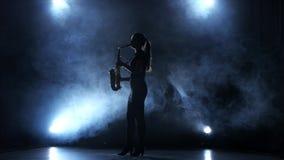 Instrumentalist woman plays on wind instrument saxophone melody. Smoky studio stock video