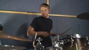 Instrumentalisten vaggar eller poppar musikern som bär i tillfällig svart t-skjorta lager videofilmer