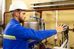 Instrumentation specialist monitors pressure. The instrumentation specialist monitors pressure sensors in the industrial plant stock image