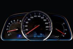 Instrumentbr?dan av bilen gl?der bl? med r?da pilar p? natten med en hastighetsm?tare, takometern och andra hj?lpmedel f?r att ?v royaltyfri fotografi