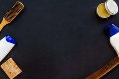 Instrumente des männlichen Friseurs mit Shampoo und des Kammes in der Draufsicht des Friseursalons über den schwarzen Hintergrund lizenzfreies stockbild