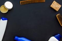 Instrumente des männlichen Friseurs mit Shampoo und des Kammes in der Draufsicht des Friseursalons über den schwarzen Hintergrund stockbilder