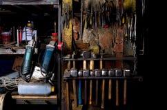 Instrumentenhulpmiddelen op de muur in workshop zoals molen, buigtang, hamer en andere Stock Foto