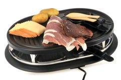 Instrumento e alimento para fazer um raclette fotos de stock