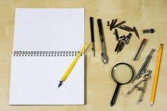 Instrumentos de dibujo y un cuaderno en la tabla de trabajo Accessorie Imágenes de archivo libres de regalías