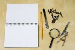 Instrumentos de dibujo y un cuaderno en la tabla de trabajo Accessorie Foto de archivo libre de regalías