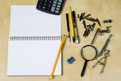 Instrumentos de dibujo y un cuaderno en la tabla de trabajo Accessorie Imagen de archivo libre de regalías