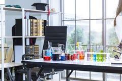 Instrumentos del laboratorio Agua del color en tubo de ensayo y cubilete Imagen de archivo libre de regalías