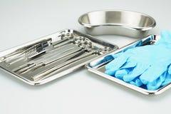 Instrumentos médicos e luvas azuis em uma bandeja de aço inoxidável Fotografia de Stock