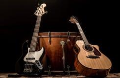 instrumentos musicales, guitarra acústica del barril del bombo y guitarra baja en un fondo negro Fotografía de archivo