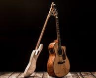 instrumentos musicales, guitarra acústica del barril del bombo y guitarra baja en un fondo negro Imágenes de archivo libres de regalías