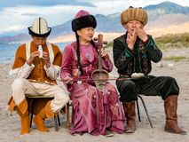 Instrumentos tradicionales del juego de los músicos en Issyk Kul Imagenes de archivo