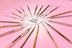 Instruments dentaires dans la forme de coeur sur le fond rose images stock