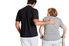Instrutor Assisting Senior Woman com seu caminhante Fotografia de Stock Royalty Free