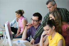 Instrutor com adultos novos em uma sala de conferências Fotografia de Stock Royalty Free