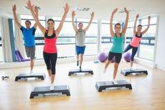 Instrutor com a classe da aptidão que executa o exercício da ginástica aeróbica da etapa Imagem de Stock Royalty Free